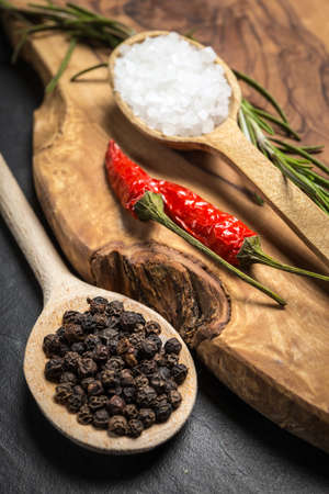 Chili with black pepper and salt on rustic wooden table. Stock Photo