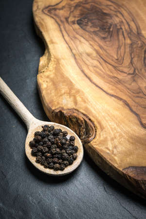 burl wood: black pepper on rustic wooden table with copy space Stock Photo