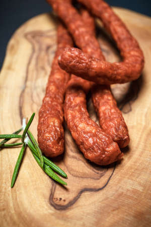 pancetta cubetti: Closeup of fresh thin sausages on wooden background