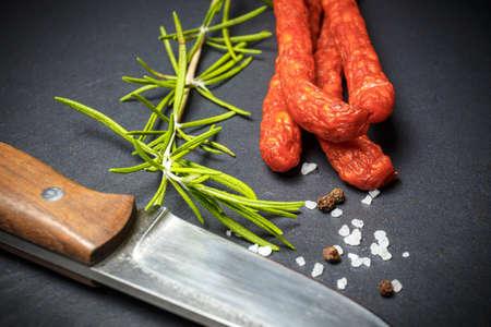 pancetta cubetti: Primo piano di salsicce sottili freschi su sfondo nero di pietra con coltello