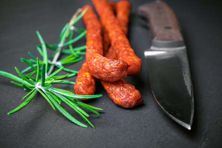 pancetta cubetti: Closeup of fresh thin sausages on black stone background with knife Archivio Fotografico