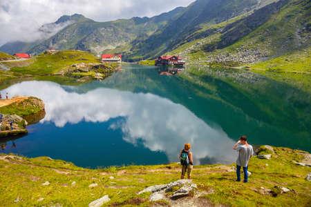 BALEA LAKE, ROMANIA - 21 JULY, 2014: Unidentified tourists enjoy the sights of Balea Lake at 2,034 m altitude in Fagaras Mountains, Romania.