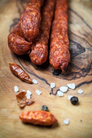 pancetta cubetti: Close up di salsicce fresche sottili su sfondo di legno Archivio Fotografico