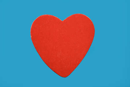 Red wooden heart isolated on blue background Stock Photo