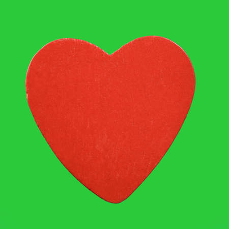 Red wooden heart isolated on green background