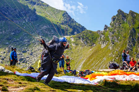 balea: Balea Lake, Romania - JULY 21, 2014: Unidentified paraglider in Balea Lake, Fagaras Mountain, Romania. Paragliding is one of the most popular adventure sports in the world