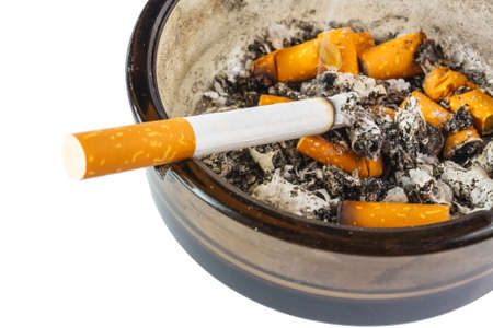 Ciérrese para arriba de cigarrillo en cenicero en el fondo blanco