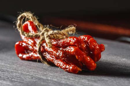 pancetta cubetti: Salsicce secche sul tagliere di legno, vicino