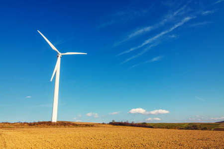 wind turbine on blue sky background, energy and economy concept Stock Photo