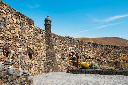 Windmill in tropical cactus garden in Guatiza village, popular attraction in Lanzarote, Canary islands Stock Photo