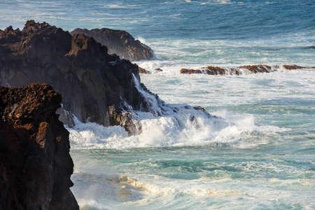 Los Hervideros, volcanic coastline with wavy ocean and blue sky, Lanzarote island, Spain