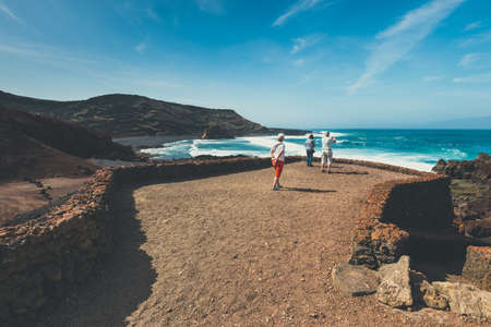 crater lake: LANZAROTE, SPAIN - March 30, 2017: Unidentified people walking  in El Golfo and Green Lagoon. The Gulf is a lagoon in a volcanic crater surrounded by steep cliffs.