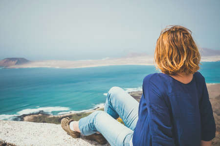 far away look: Young woman sitting on stone fence looking at sea