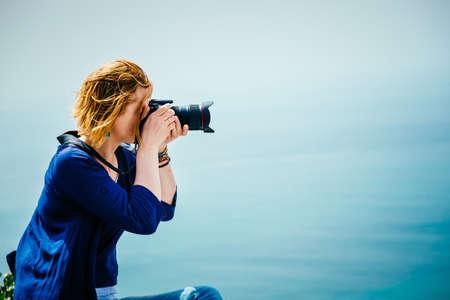 far away look: Female traveler taking a photo on the seaside Stock Photo