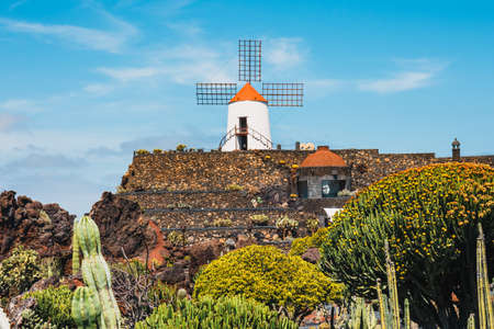 Windmill in tropical cactus garden in Guatiza village, popular attraction in Lanzarote, Canary islands Stock Photo