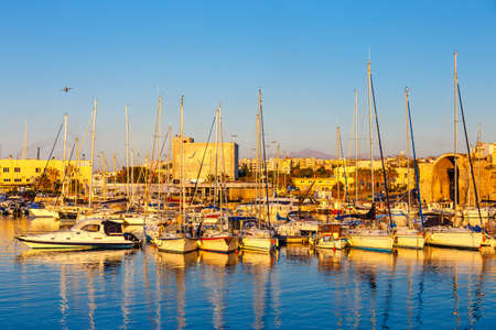 morning blue hour: Heraklion, Greece, June 10, 2017: Old harbour of Heraklion with fishing boats and marina during twilight, Crete, Greece