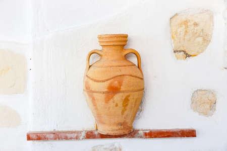 Greek style ceramic vase on white wall background Stock Photo