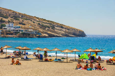 decade: Crete Island, Greece, June 09, 2017: Panorama of Matala beach. Caves on the rocks were used as a roman cemetery and at the decade of 70s were living hippies from all over the world, Crete, Greece