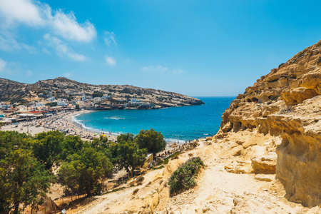Matala beach. Caves on the rocks were used as a roman cemetery and at the decade of 70's were living hippies from all over the world, Crete, Greece Banco de Imagens - 83186617