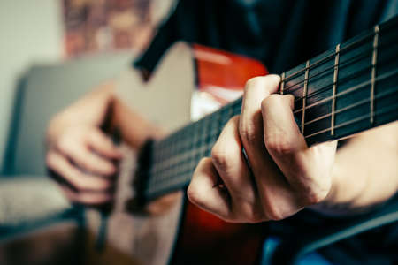 young musician playing acoustic guitar, live music background photo