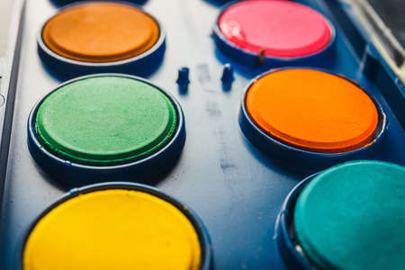 Watercolor paints in a box with paintbrush, close up Stock Photo