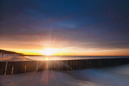 Sunset on the beach with a wooden breakwater, long exposure Stock Photo