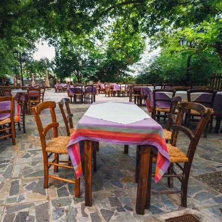 Empty greek tawern in the garden, Crete Island, Greece Stock Photo
