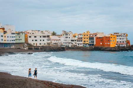 Puerto de la Cruz, Tenerife, Spain - June 08, 2015: Unknown people are walking and relaxing on the beach with colour houses in the background, Puerto de la Cruz, Tenerife Island, Spain