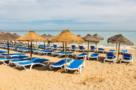 Lounge chairs and straw umbrellas at the beach. Costa del Sol, Andalusia, Spain