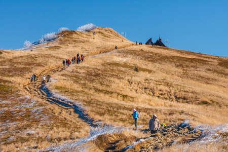 Wetlina, Poland, November 12, 2011: A group of tourists hiking on a trail in Polonina Wetlinska on a sunny day, Bieszczady Mountains in Poland Zdjęcie Seryjne - 128136346