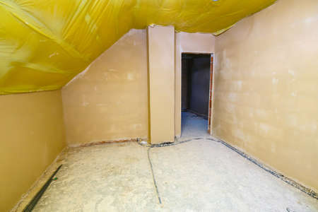 Empty room in a house under construction with fresh screed and plaster