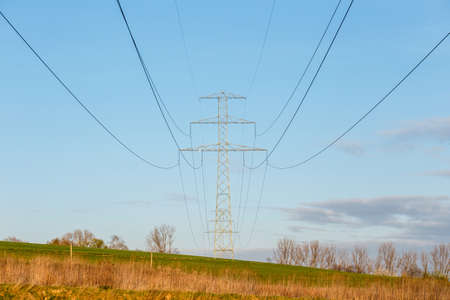Steel high voltage poles and electric wire with blue sky and fields in rural areas. Stock Photo