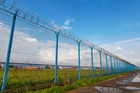 Barbed wire fence of the restricted area under blue sky