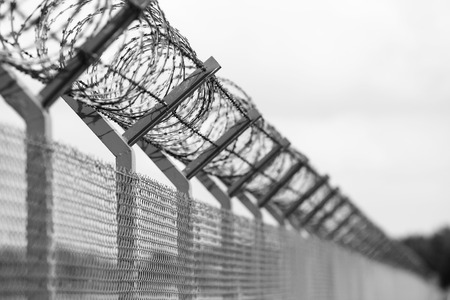 guantanamo: Barbed wire fence of the restricted area, black and white Stock Photo