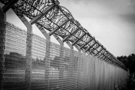 guantanamo: Barbed wire fence of the restricted area, black and white vignette picture Stock Photo