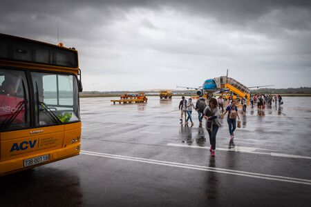 Dong Hoi airport, Vietnam - March 8 2017: people walking across airport board without waiting for shuttle bus.