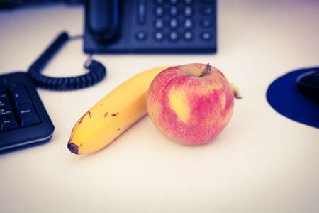 Healthy eating at work, apple and banana on the desk, yellow and purple duotone color