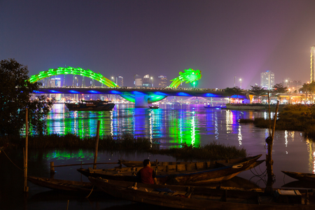 pm: DA NANG, VIETNAM - March 12, 2017: illuminated Dragon River Bridge over Han River, Cau Rong (Rong Bridge). Every weekend at 9 p.m. there is show fire and water breathing. First theres is a fire blast from dragons head and afterwards water is sprayed ou