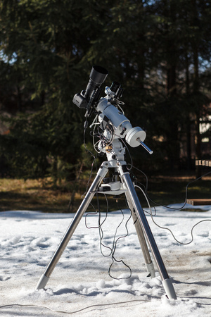 Professional astrophotography setup equipped with DSLR camera, telephoto lens and guider scope ready for night session Stock Photo