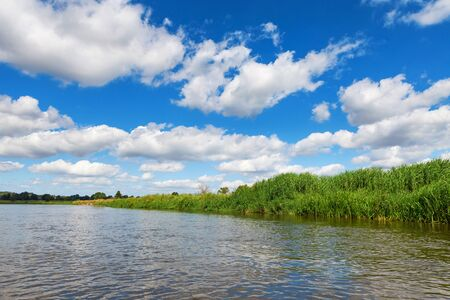Blue cloudy summer sky over Bug river, Poland, Europe