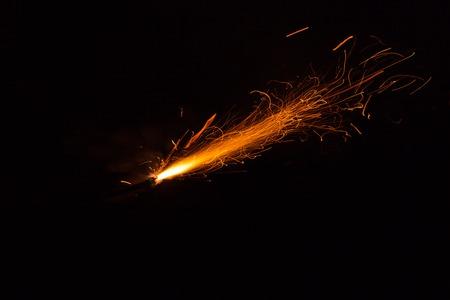 Burning fuse with sparks on black background