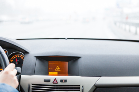 Slippery road warning on car display, car interior point of view