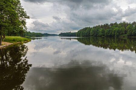 Reflection of moody sky in calm lake Фото со стока - 127582746