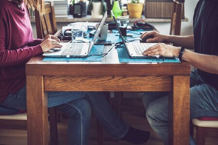 Couple working from home during coronavirus pandemic. Candid image of man and woman sitting at one table with their laptops and other stuff nearby.