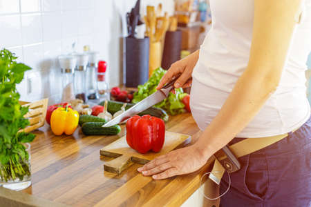 Pregnant woman with insuline pump preparing healthy food in the kitchen.