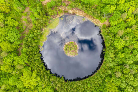 Round lake with island in the middle among forest, aerial view