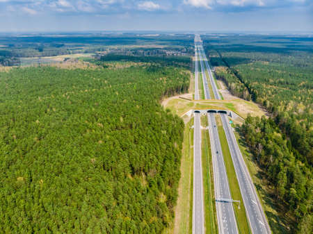 Expressway with ecoduct crossing - bridge over a motorway that allows wildlife to safely cross over the road, aerial top down view