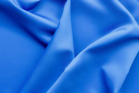 Elegant soft abstract blue background. Delicate silk waved fabric with copy space for design projects Фото со стока