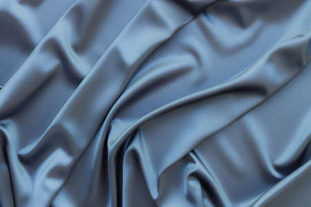 Elegant soft abstract gray background. Delicate silk waved fabric with copy space for design projects. Toned image.
