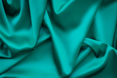 Elegant soft abstract green background. Delicate silk waved fabric with copy space for design projects